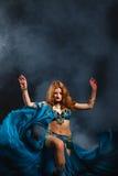 Frau im Karnevalskostüm mit einem Fan auf Schwarzem Stockfoto