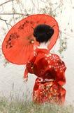 Frau im Kimono mit dem roten Regenschirm, hintere Ansicht Stockfotografie
