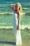 Frau im Kleid auf Küste Stockfotos