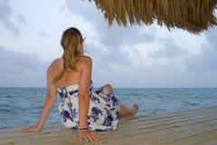 Frau im Kleid, das auf Ozeandock sitzt Stockfotos