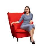 frau im roten kleid das auf einem wei en stuhl sitzt. Black Bedroom Furniture Sets. Home Design Ideas