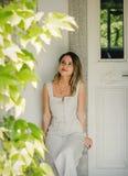 Frau im Kleid, das in einem Schatten eines Gebäudes am sonnigen Tag sich versteckt lizenzfreies stockfoto