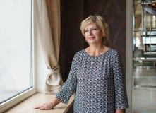 Frau im Kleid, das nahe einem Fenster steht Stockbilder