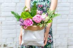 Frau im Kleid mit Blumenstrauß von Pfingstrosen in Kraftpapier-Tasche Stockfotografie