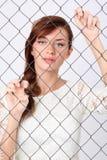 Frau im Kleid steht hinter Metallmasche und hält sie an Lizenzfreie Stockfotos