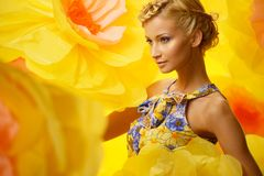 Frau im Kleid unter großen gelben Blumen Lizenzfreies Stockfoto