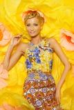 Frau im Kleid unter großen gelben Blumen Lizenzfreies Stockbild