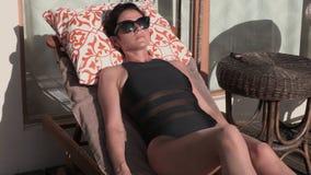 Frau im Klubsessel nahe dem Bungalow stock video