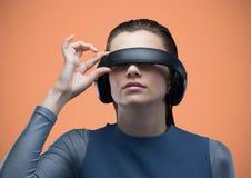 Frau im Kopfhörer der virtuellen Realität gegen orange Hintergrund Lizenzfreie Stockbilder