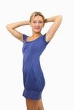 Frau im kurzen, hautengen, blauen Kleid, hält Hände hinter ihrem Kopf. Stockbild