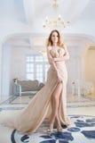 Frau im langen beige Kleid in Innen, Luxus Lizenzfreie Stockfotos