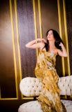 Frau im langen goldenen Kleid Stockbild