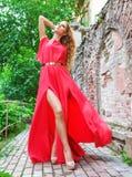 Frau im langen roten Kleid draußen Stockfotografie