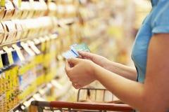 Frau im Lebensmittelgeschäft-Gang des Supermarktes mit Kupons Lizenzfreies Stockfoto