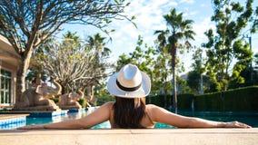Frau im Luxuskurort nahe dem Swimmingpool Lizenzfreie Stockfotos