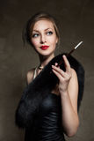 Frau im Luxuspelz Retro- Art Dunkler Hintergrund Stockfoto