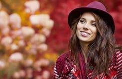 Frau im Mantel mit Hut und Schal im Herbst parken Lizenzfreie Stockfotos