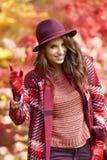 Frau im Mantel mit Hut und Schal im Herbst parken Stockfotografie