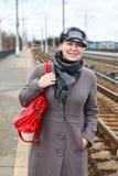 Frau im Mantel und in der Schutzkappe mit rotem Beutel lizenzfreie stockbilder