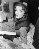 Frau im Mantel und im Hut eine Zeitschrift lesend (alle dargestellten Personen sind nicht längeres lebendes und kein Zustand exis lizenzfreie stockfotos