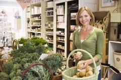 Frau im Markt, der das Kartoffellächeln betrachtet Stockfotos