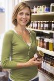 Frau im Markt, der das Konservelächeln betrachtet Stockbild