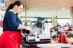 Frau im MetzgereienAusschnittspeck mit Maschine Lizenzfreies Stockbild