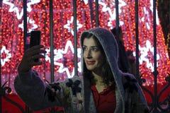 Frau im Nachtweihnachten unter Verwendung des Smartphoneschirmnehmens Lizenzfreies Stockfoto