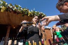 Frau im nationalen georgischen Kostüm gießt Wein in ein Glas während des Festivals Stockfotografie