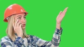 Frau im orange Sturzhelm, der einen Telefonanruf das Problem mit Gegenstand auf einem grünen Schirm, Farbenreinheits-Schlüssel be stock video footage