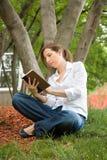 Frau im Park ein Buch lesend Lizenzfreie Stockfotografie
