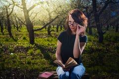 Frau im Park im Freien mit Tablette und Buch Stockfotos