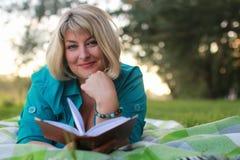 Frau im Park mit Buch auf dem Gras Lizenzfreie Stockbilder