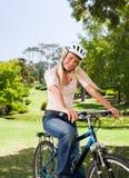 Frau im Park mit ihrem Fahrrad Lizenzfreies Stockbild