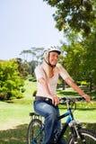 Frau im Park mit ihrem Fahrrad Lizenzfreie Stockfotografie
