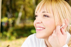 Frau im Park mit Kopfhörern Stockbild