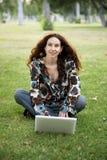 Frau im Park mit Laptop Stockfotografie