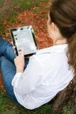 Frau im Park mit mobiler Tablette Stockfoto