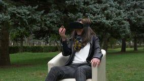 Frau im Park unter Verwendung eines VR-Kopfhörers und des Lächelns und des Betrachtens eines pinecone stock footage