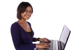 Frau im Purpur auf dem Laptoplächeln lizenzfreies stockfoto