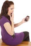 Frau im Purpur zurück entsetzt am Telefonbildschirm Lizenzfreie Stockbilder