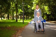 Frau im Rollstuhl, der in Park antreibt Stockfotografie