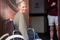 Frau im Rollstuhl vor Einstiegstür Lizenzfreies Stockfoto
