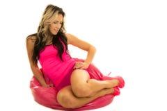 Frau im Rosa auf Knien einer Rosabohnentasche vorwärts Stockbild