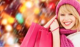 Frau im rosa Hut und im Schal mit Einkaufstaschen Lizenzfreies Stockbild