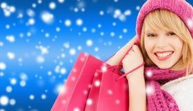 Frau im rosa Hut und im Schal mit Einkaufstaschen Lizenzfreie Stockfotos