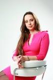 Frau im rosa Kleid, das auf dem Bürostuhl sitzt Stockbild