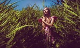 Frau im rosa Kleid im fantastischen hohen Gras Lizenzfreie Stockbilder