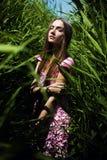 Frau im rosa Kleid im Sonnenlicht im Gras Stockbild