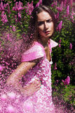 Frau im rosa Kleid mit Fliegenblumen Stockbild